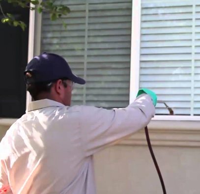 pest controller spraying a house